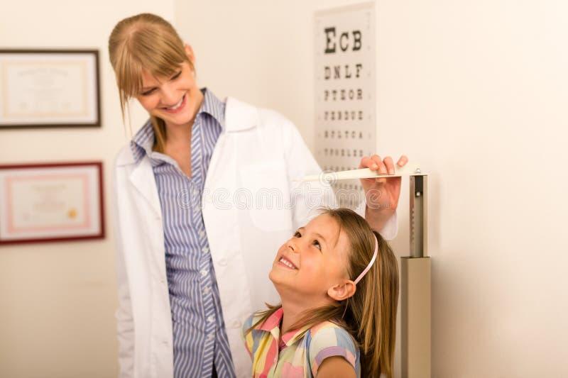 Altura de la medida del pediatra de la niña fotografía de archivo libre de regalías