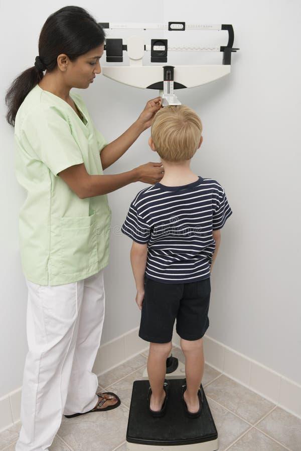 A altura de Measuring Boy da enfermeira fotografia de stock royalty free