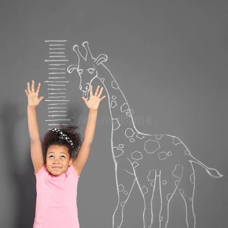 Altura de medição da criança afro-americano perto do desenho do girafa do giz na parede fotos de stock