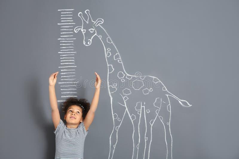 Altura de medición del niño afroamericano cerca del dibujo de la jirafa de la tiza en gris foto de archivo libre de regalías
