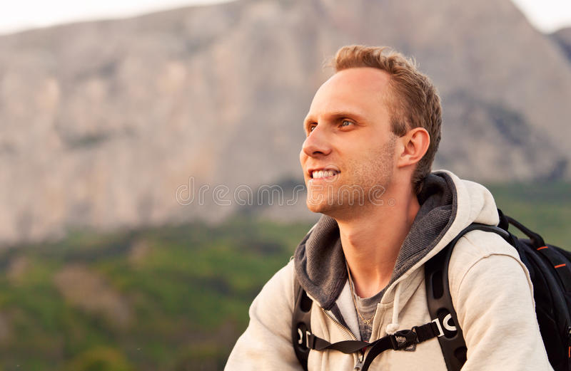 A altura do homem novo aprecia após a escalada na montanha imagem de stock
