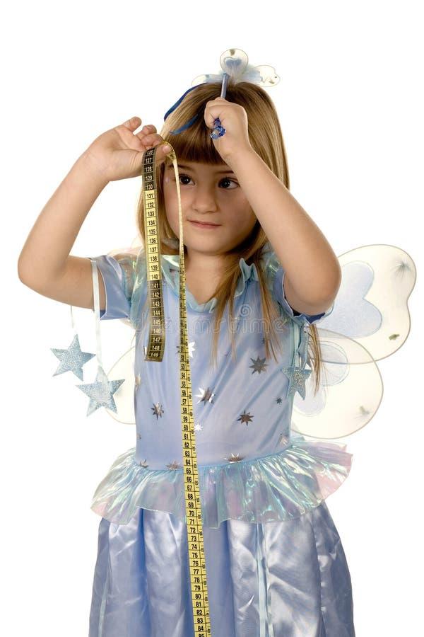 Altura masuring da menina feericamente adorável fotografia de stock