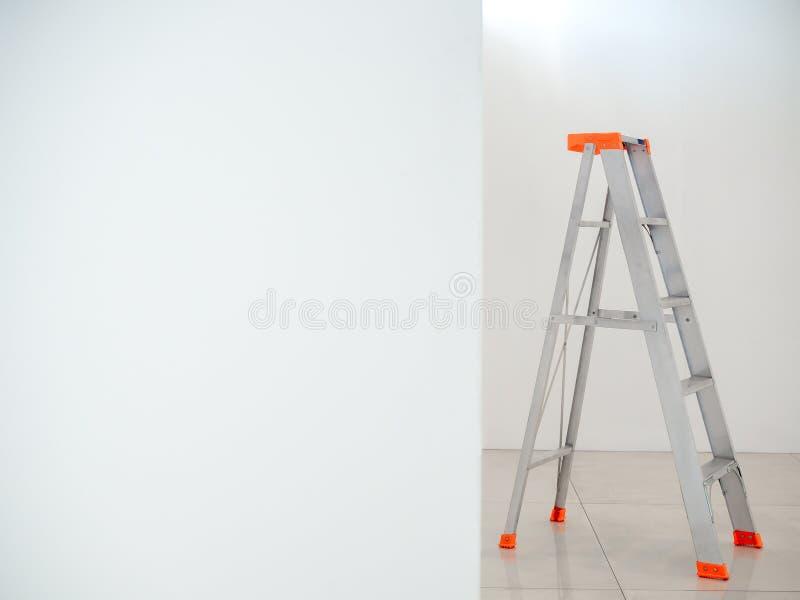 Aluminiowa falcowanie drabina Krok drabina na biel ściany tle zdjęcia stock