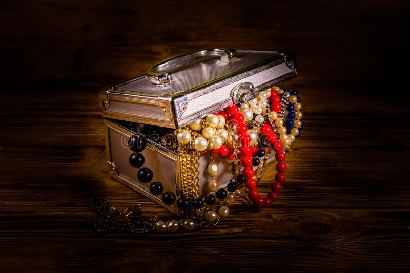 Aluminiowa skrzynka pełno różna biżuteria na drewnianym stole zdjęcie stock