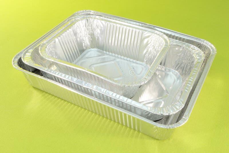 Aluminium catering trays. Three aluminium catering trays isolated on green background stock photos