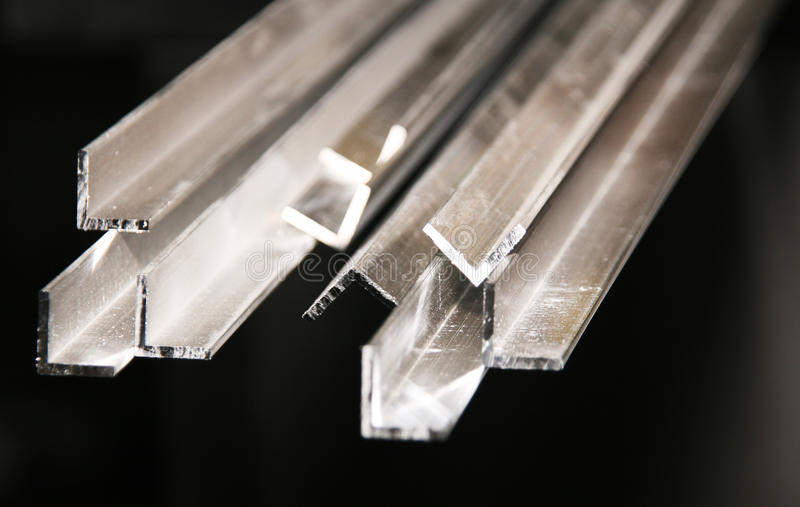 Aluminium extrusions. With focus on sawn off ends on a black background stock photo