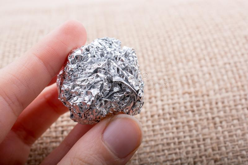 Aluminium foil in the shape of a sphere on textured background stock images