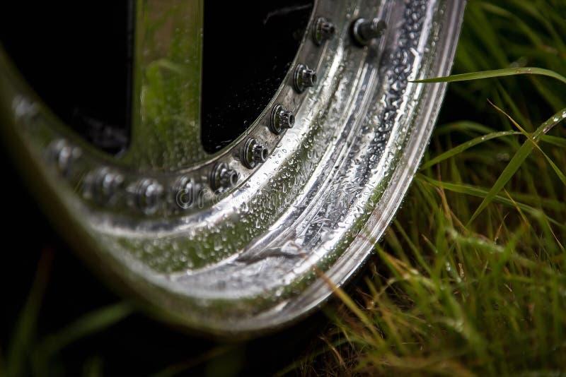 Aluminium gesmede wielen op het groene gras in paardebloemen Poolse randen met regendruppels op het en bouten stock fotografie