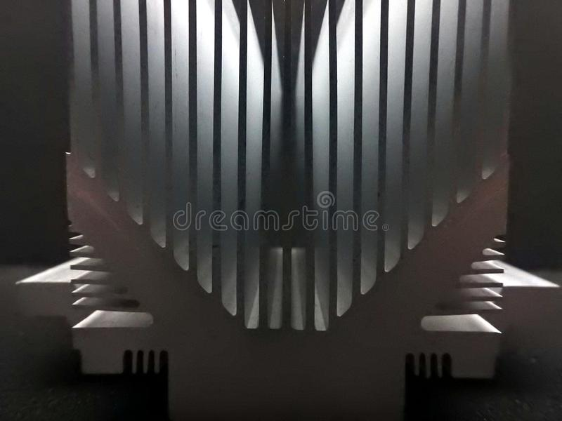 Aluminium heat absorber. Closeup of aluminium heat absorber with fins to increase air circulation and the cooling efficiency in computers , dark background royalty free stock photos