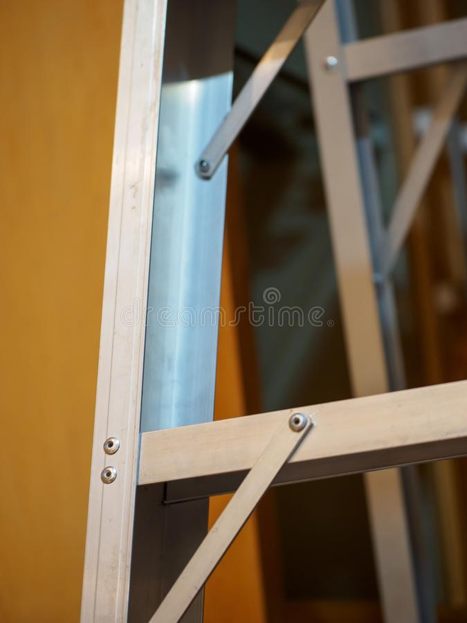 Aluminium ladder, dark wall, vertical royalty free stock images