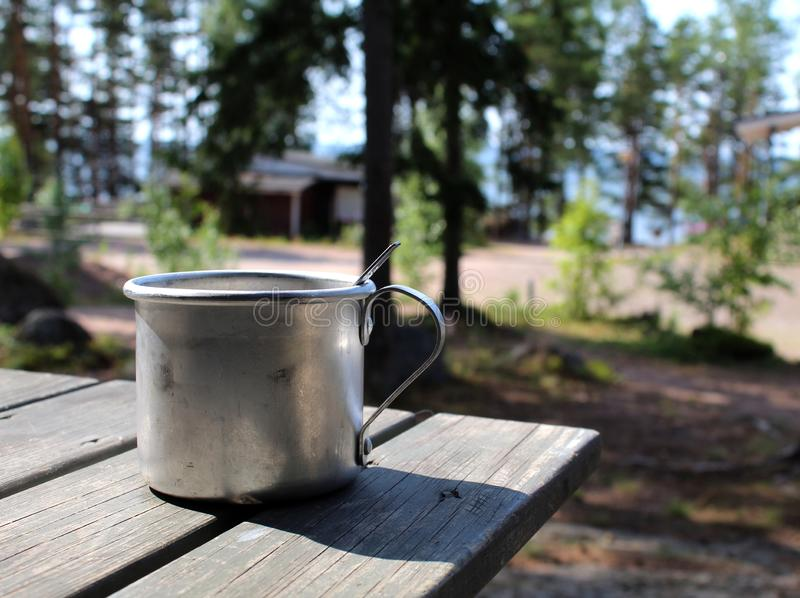 Aluminium mug for camping on a wooden table in a campsite in Finland stock image