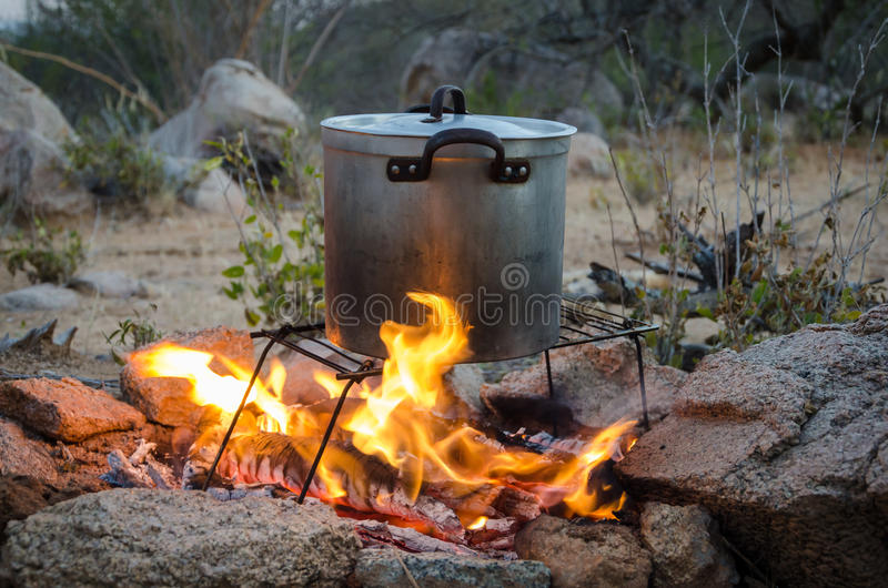 Aluminium pot being heated over outdoor camp fire. Aluminium pot standing on foldable grill being heated over outdoor camp fire surrounded by rocks royalty free stock photo