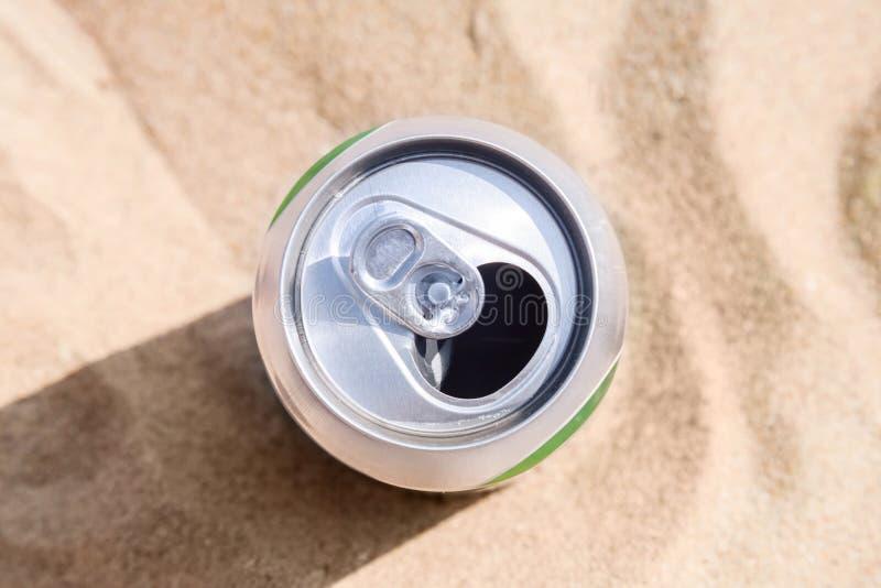 Aluminiumburken av öl står på strandsand arkivbild
