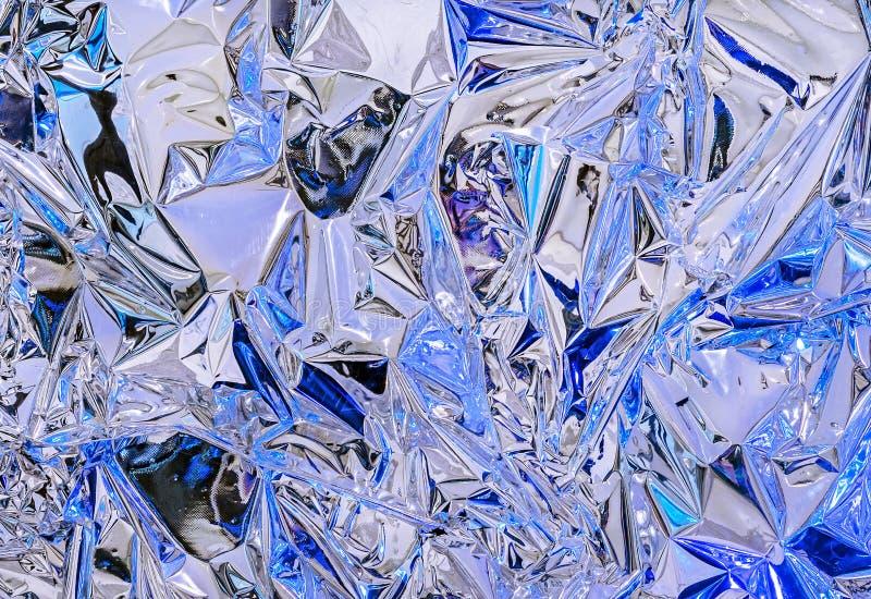 Aluminiumfolie met multi-colored verlichting Achtergrond en textuur van aluminiumfolie stock afbeelding