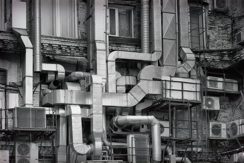 Aluminiumlüftungsrohre außerhalb des alten Industriegebäudes der Fabrik, neu gemacht nach innen in einem modernen Büro schwarzes lizenzfreie stockfotos