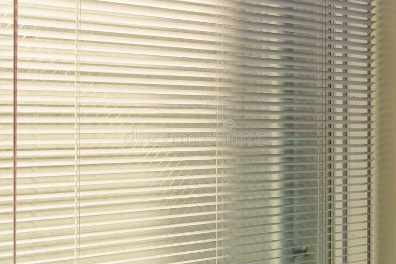 Aluminiumpersienner med solljus som kommer från ett fönster Garneringinre fotografering för bildbyråer