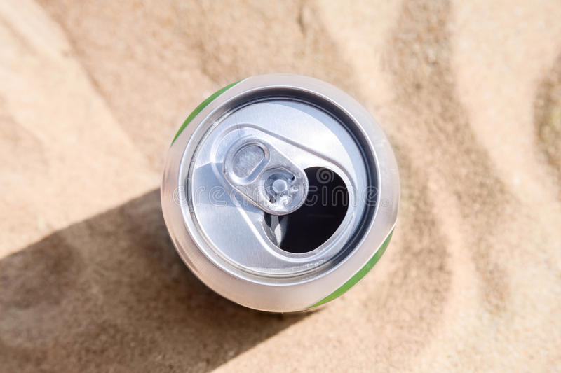 Aluminum can of beer stands on beach sand stock photography