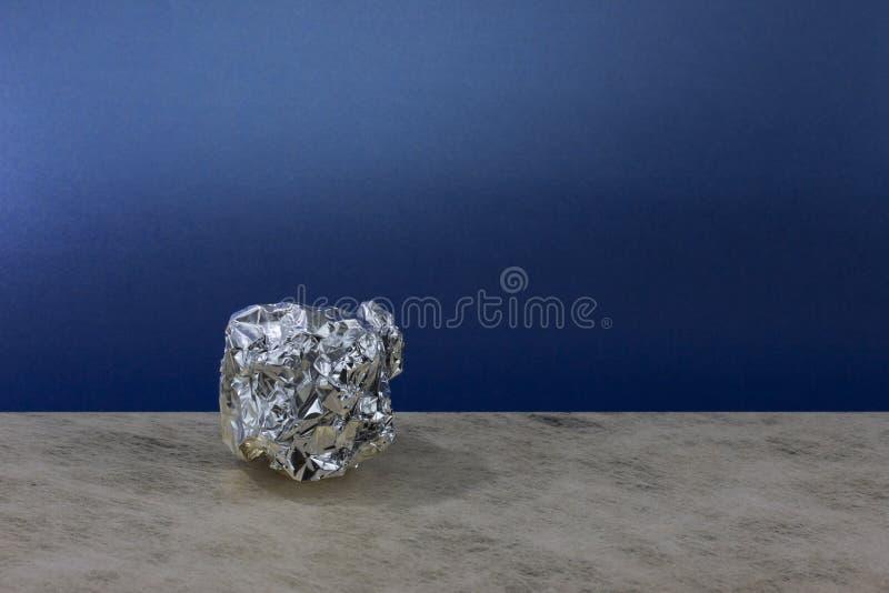 Aluminum foil ball on blue background stock photos