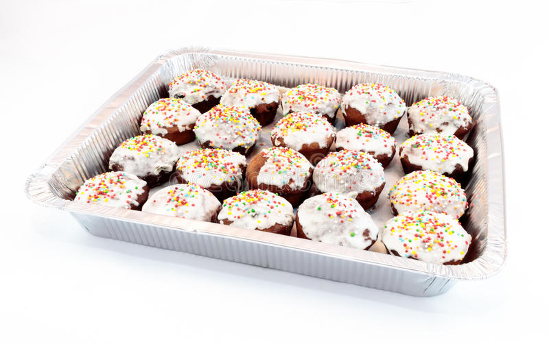 Aluminum foil tray filled with Easter cakes of homemade cakes, d. Ecorated with glaze and small round colored candies on a white background stock photos