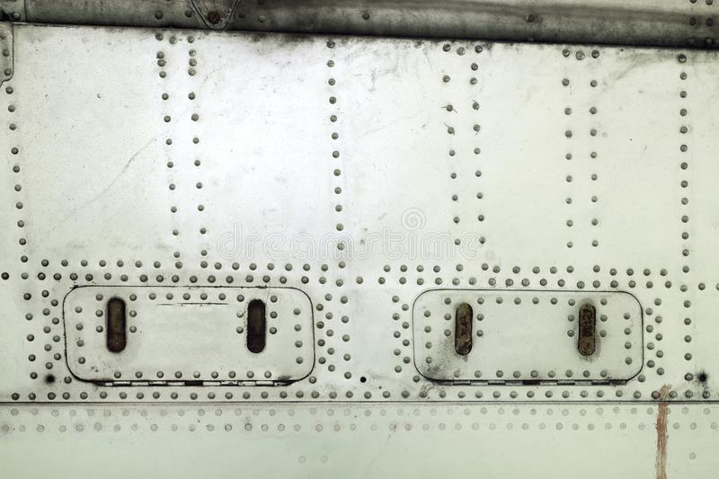 Aluminum surface of the aircraft fuselage. Rivets and hatches. Weather, scratched and corrosive surface stock photography