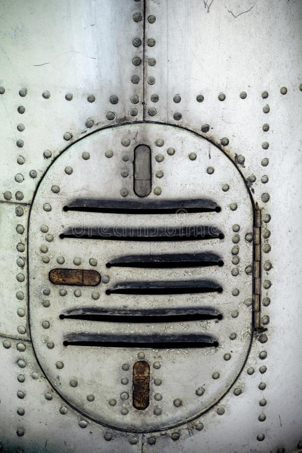 Aluminum surface of the aircraft fuselage. Rivets and hatches. Weather, scratched and corrosive surface royalty free stock image