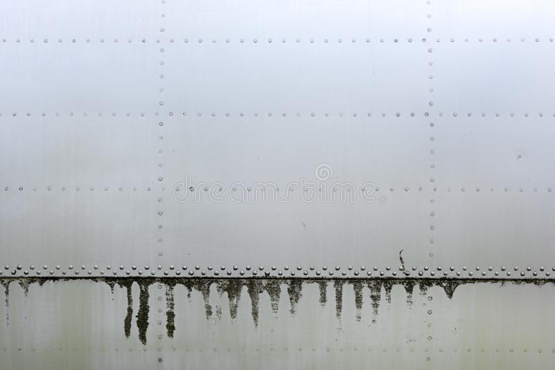 Aluminum surface of the aircraft fuselage. Smooth rows of rivets, there are scratches, dirt and oil stains royalty free stock photos