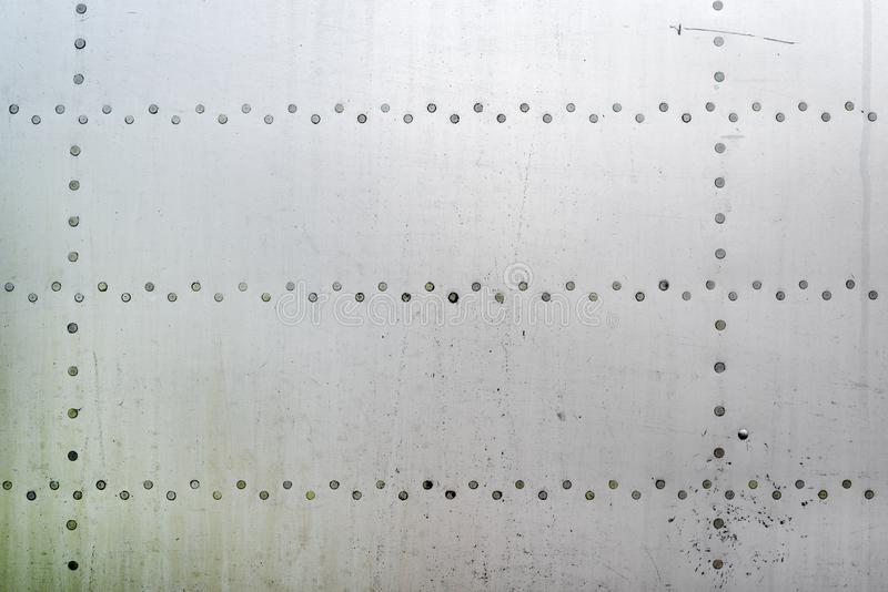 Aluminum surface of the aircraft fuselage. Smooth rows of rivets, there are scratches, dirt royalty free stock image