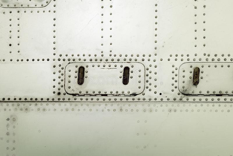 Aluminum surface of the aircraft fuselage. Rivets and hatches. Weather, scratched and corrosive surface royalty free stock photography