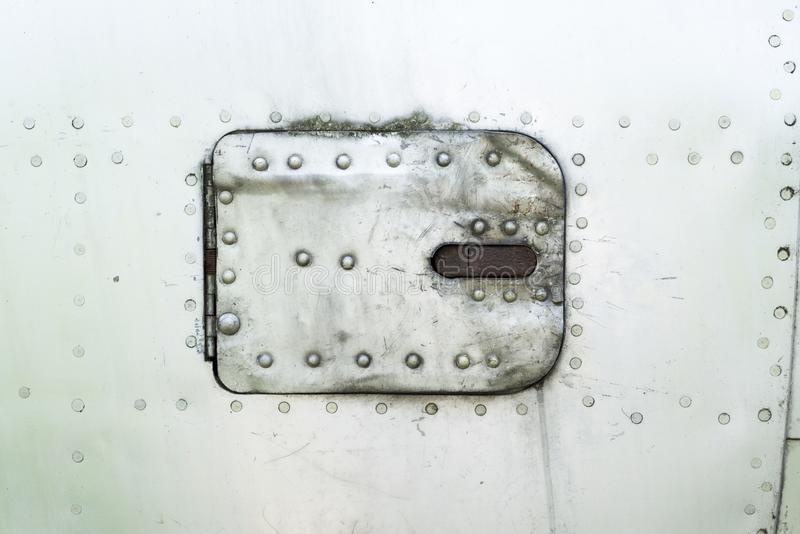 Aluminum surface of the aircraft fuselage. Rivets and hatches. Weather, scratched and corrosive surface stock photos