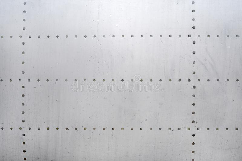 Aluminum surface of the aircraft fuselage. Smooth rows of rivets, there are scratches, dirt royalty free stock photo