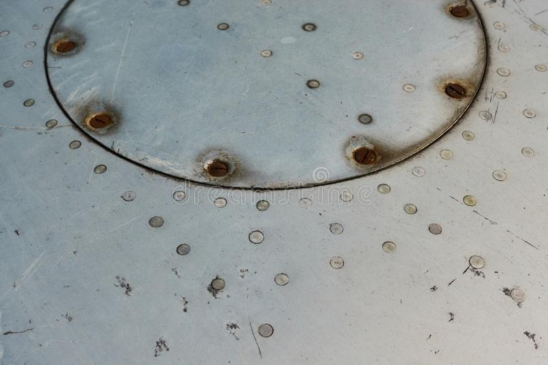 Aluminum surface of the aircraft fuselage. Smooth rows of rivets, there are scratches, dirt stock photography