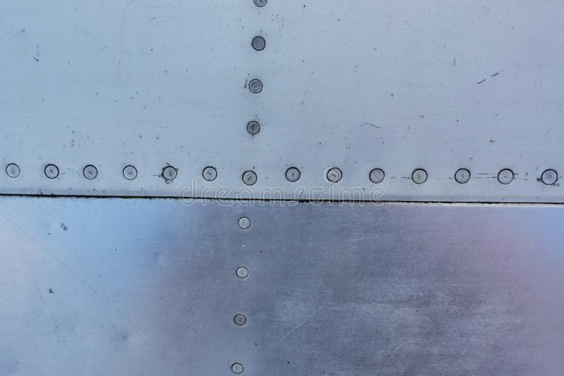 Aluminum surface of the aircraft fuselage. Smooth rows of rivets, there are scratches, dirt royalty free stock photos