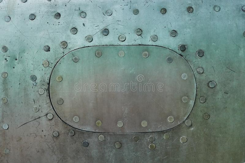 Aluminum surface of the aircraft fuselage. Smooth rows of rivets, there are scratches, dirt stock images