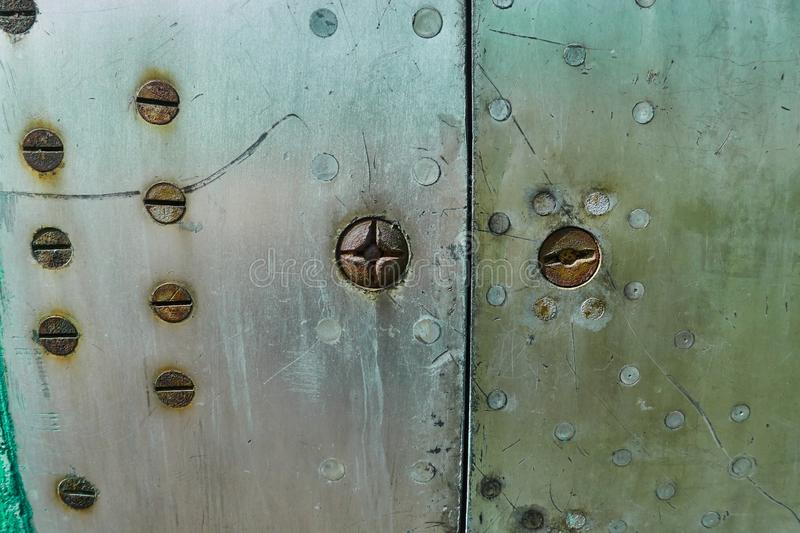 Aluminum surface of the aircraft fuselage. Smooth rows of rivets, there are scratches, dirt stock image