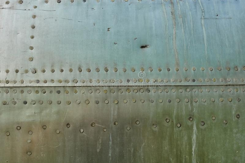Aluminum surface of the aircraft fuselage. Smooth rows of rivets, there are scratches, dirt royalty free stock photography