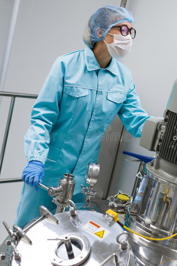 The operator checks the equipment for the production of sterile stock images