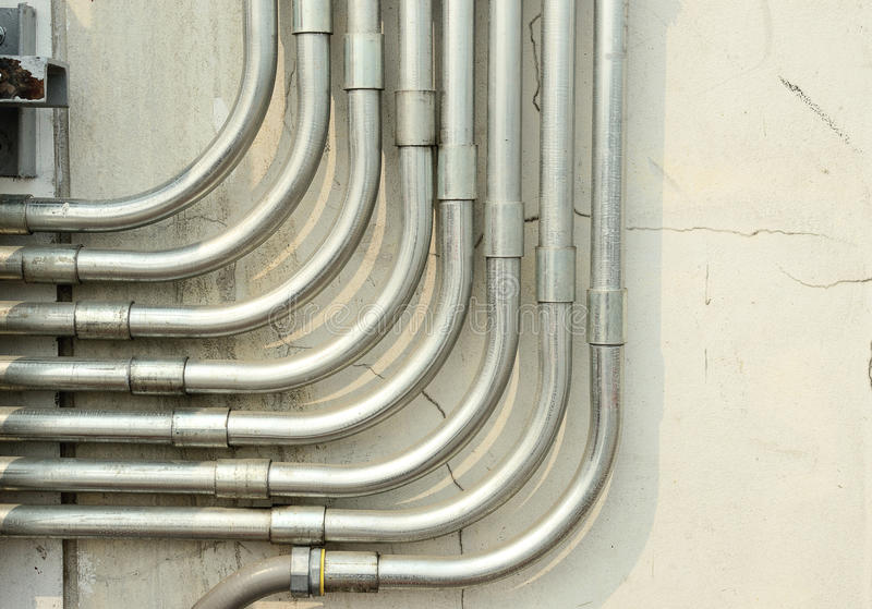Aluminum tubing for wire protection lined. Up on the old concrete wall royalty free stock photos