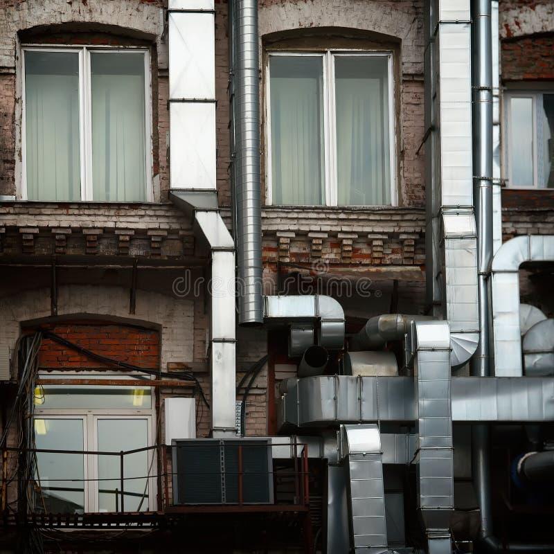 Aluminum ventilation leda i rör utanför den gamla industriella tegelstenbyggnaden av fabriken som göras om inom i ett modernt kon arkivfoto