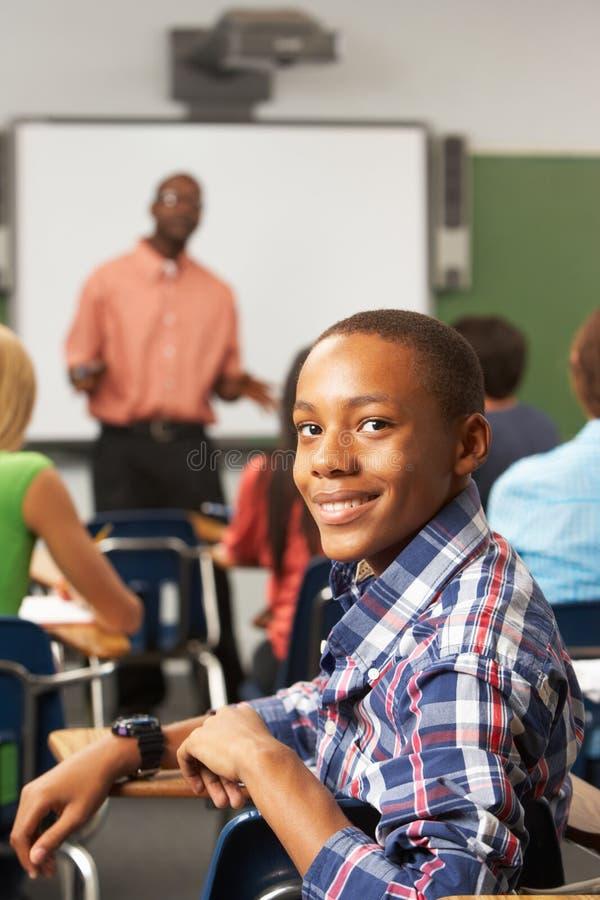Alumno adolescente masculino en sala de clase foto de archivo