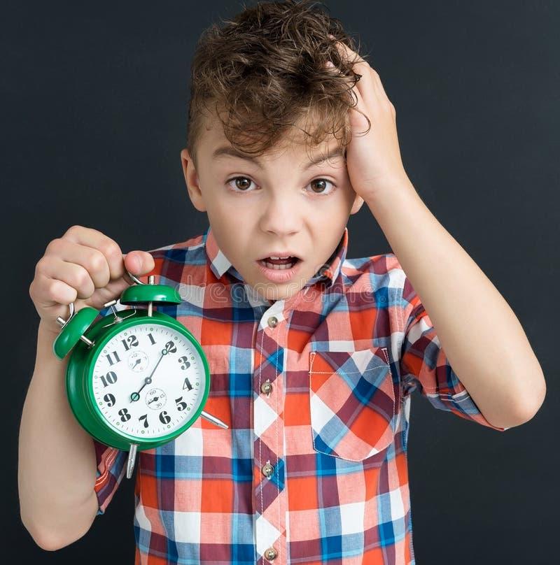 Alumno chocado con el despertador verde grande - de nuevo a concep de la escuela imágenes de archivo libres de regalías