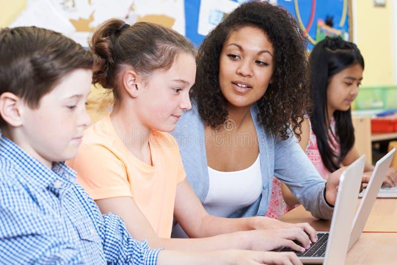 Alumno de Helping Female Elementary del profesor en clase del ordenador fotografía de archivo libre de regalías