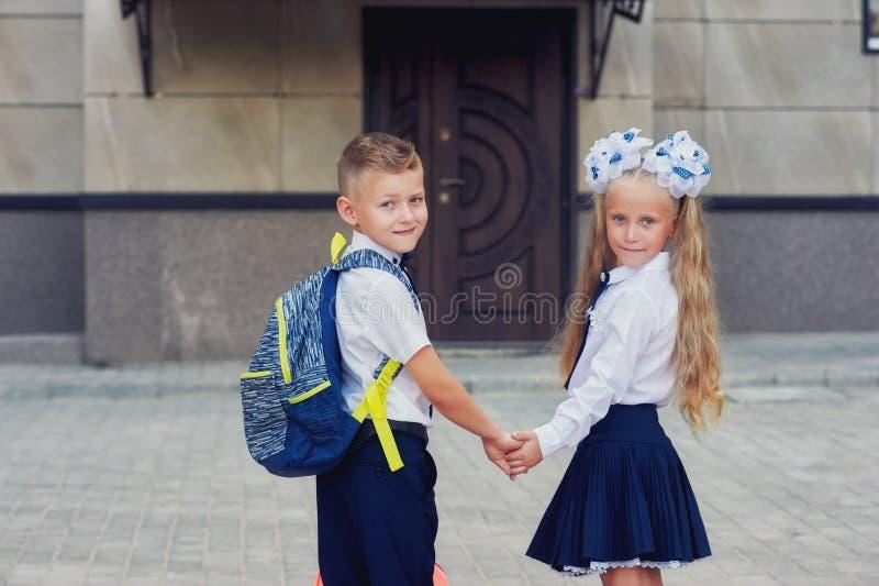 Alumno de la escuela primaria Niños con las mochilas cerca de la construcción de escuelas fotografía de archivo libre de regalías