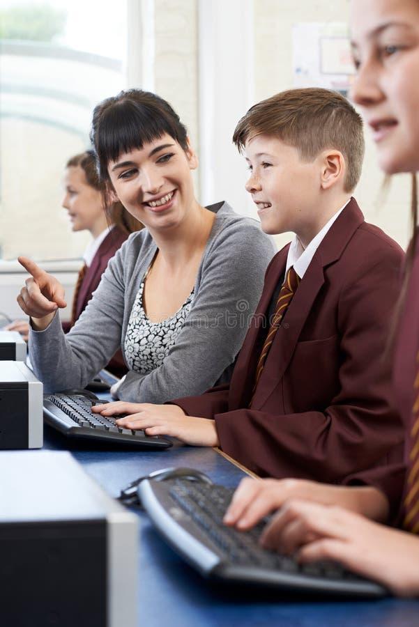 Alumno elemental masculino en clase del ordenador con el profesor imagen de archivo