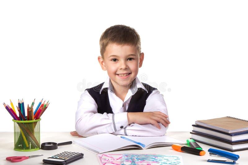 Alumno excelente alegre sonriente todavía que se sienta en el escritorio con el fondo blanco imagen de archivo