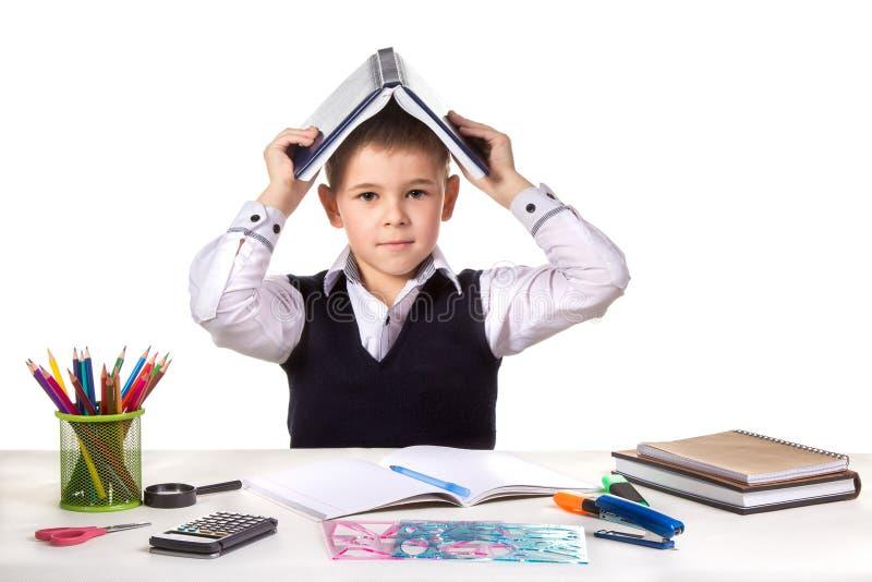 Alumno excelente serio elegante en el escritorio con el libro abierto en la cabeza en el fondo blanco fotos de archivo