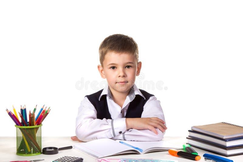Alumno excelente serio elegante todavía que se sienta en el escritorio con el fondo blanco fotografía de archivo libre de regalías