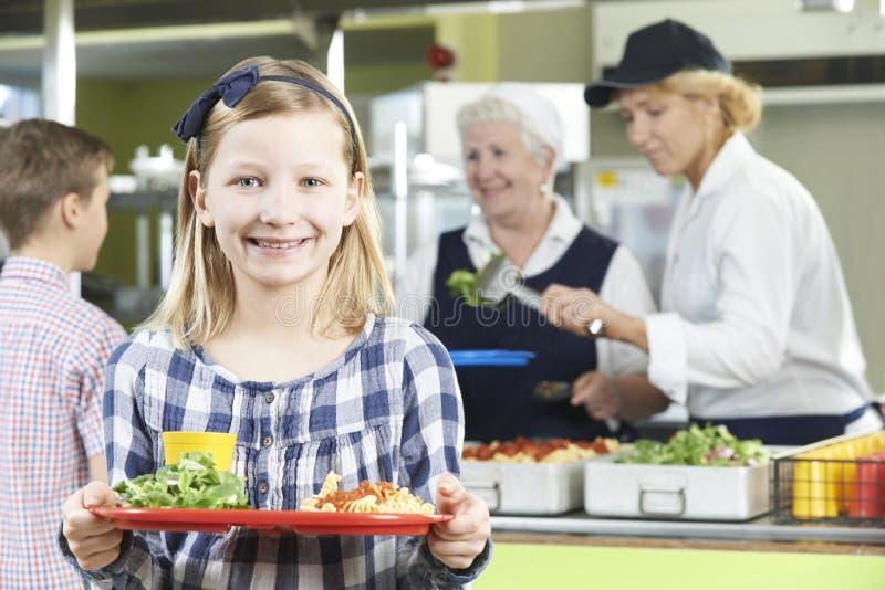 Alumno femenino con el almuerzo sano en cantina de la escuela fotos de archivo libres de regalías