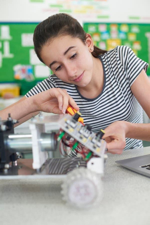 Alumno femenino en la lección de la ciencia que estudia la robótica foto de archivo