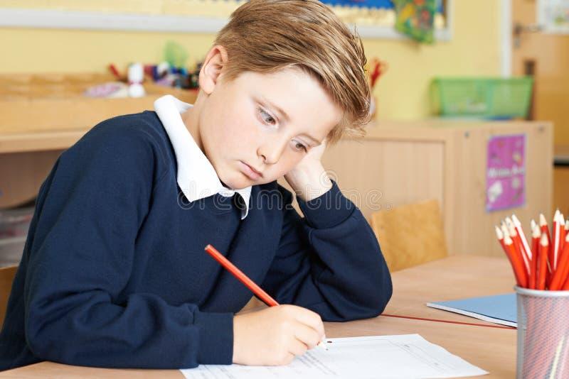 Alumno masculino agujereado de la escuela primaria en el escritorio fotografía de archivo libre de regalías