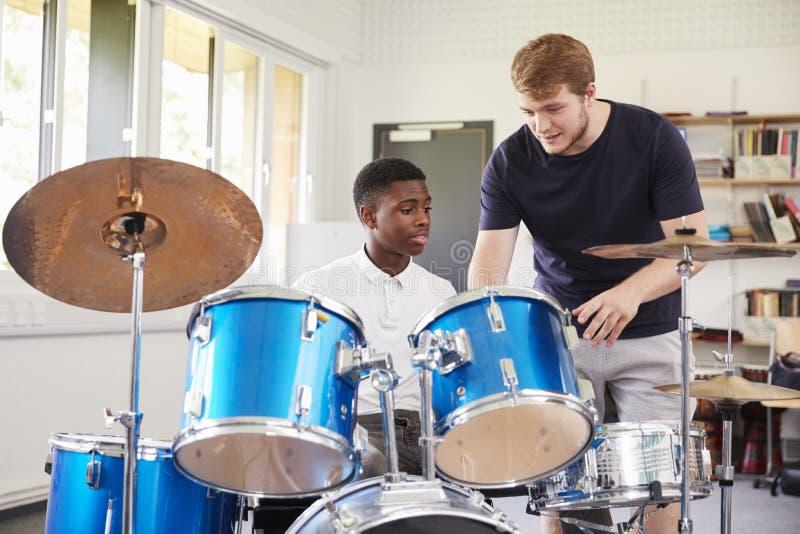 Alumno masculino con la lección de música de Playing Drums In del profesor fotos de archivo libres de regalías